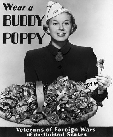 """1950 --- 1950- Doris Day, nationally famous Warner Brothers motion picture, & favorite recording radio star, selected by the Veterans of Foreign wars as their 1950 Buddy Poppy Girl, is a uniquely appropriate choice for the annual national sale of Buddy Poppies, made by disabled ex-service men, to raise funds for rehabilitation and welfare work. Her outstanding success despite a crippling accident in her 'teens, is a strikig example of courage to """"carry on"""". Miss Day was a member of the Bob Hope entertainment troupe which visited military installations and hospitals throughout the country. --- Image by © Bettmann/CORBIS"""