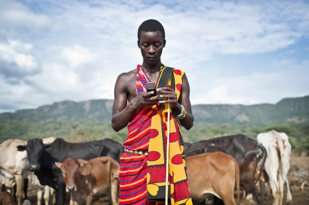 saac Mkalia, 20 years old, a teacher by profession is checking his mobile phone.