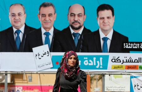 A woman walks past a Joint Arab List campaign billboard in Umm el-Fahm