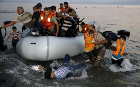 "Syrian refugees carry their children as they jump off an overcrowded dinghy upon arriving on a beach on the Greek island of Kos, after crossing a part of the Aegean sea from Turkey, August 9, 2015. United Nations refugee agency (UNHCR) called on Greece to take control of the ""total chaos"" on Mediterranean islands, where thousands of migrants have landed. About 124,000 have arrived this year by sea, many via Turkey, according to Vincent Cochetel, UNHCR director for Europe. REUTERS/Yannis Behrakis TPX IMAGES OF THE DAY - RTX1NN3R"