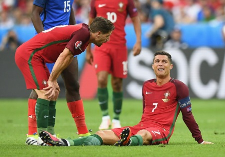 PARIS, FRANCE - JULY 10: Cristiano Ronaldo of Portugal lies injured as teammate Adrien Silva of Portugal (L) checks on him during the UEFA EURO 2016 Final match between Portugal and France at Stade de France on July 10, 2016 in Paris, France. (Photo by Laurence Griffiths/Getty Images)